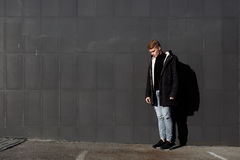 Young stylish redhead man in trendy outfit posing against urban background Royalty Free Stock Images