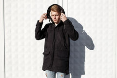 Young stylish redhead man in trendy outfit posing against urban background Royalty Free Stock Photography