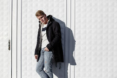 Young stylish redhead man in trendy outfit posing against urban background Stock Image