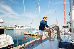 Young stylish sailor man standing on the yacht Stock Image