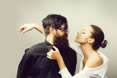 Young stylish couple in studio. Young couple of women with glamour makeup on pretty face in stylish shirt and bra near handsome bearded men with long beard and royalty free stock images