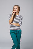Young stylish slim tanned female standing with hand on chin, on Royalty Free Stock Photo
