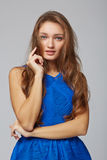 Young stylish slim tanned female standing with hand on chin, on Royalty Free Stock Images