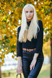 Young stylish sporty blond beautiful teen girl in black posing at park on a warm fall day against blurred yellow foliage backgrou Stock Photo