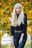 Young stylish sporty blond beautiful teen girl in black posing at park on a warm fall day against blurred yellow foliage backgrou Royalty Free Stock Photo