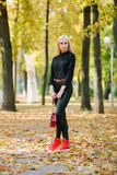 Young stylish sporty blond beautiful teen girl in black posing at park on a warm golden fall day against blurred yellow foliage ba Stock Photos