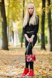 Young stylish sporty blond beautiful teen girl in black posing at park on a warm golden fall day against blurred yellow foliage ba Stock Photo