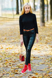 Young stylish sporty blond beautiful teen girl in black posing at park on a warm golden fall day against blurred yellow foliage ba Stock Photography