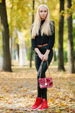 Young stylish sporty blond beautiful teen girl in black posing at park on a warm golden fall day against blurred yellow foliage ba Royalty Free Stock Photography