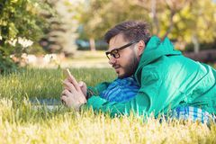 Chilling hipster in park with smartphone Stock Photography