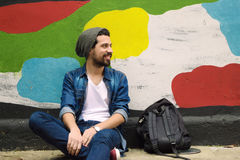 Young stylish student seated against a colorful wall. Royalty Free Stock Images