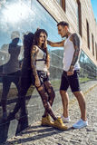 Young stylish tattooed couple at the black tiled wall on the street Royalty Free Stock Photo