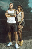 Young stylish tattooed couple standing at the tiled black wall on the street Royalty Free Stock Image