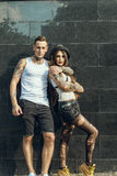Young stylish tattooed couple standing at the tiled wall on the street Royalty Free Stock Images