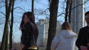 Young and stylish teenagers dancing and singing in the park. Funny friends sings and dances at the street in park. Teenagers have fun together and moving to the stock video footage