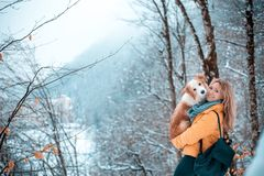 Young stylish travel woman in mountain forest, looking forward, holding a dog, happy positive mood, winter, bohemian royalty free stock photography
