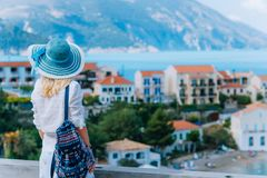 Young stylish traveler woman enjoying view of colorful tranquil Assos village. Female model wearing blue sunhat, white royalty free stock photo