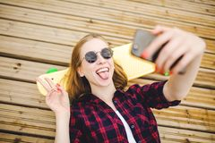 Young stylish urban girl in hipster outfit making selfie while lying with on wooden pier royalty free stock photo