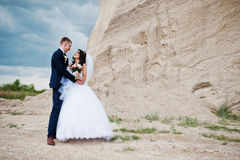 Young stylish wedding couple against sandy career at cloudy sky. Royalty Free Stock Images