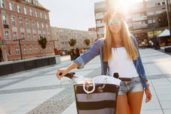 Young stylish woman with a bicycle Royalty Free Stock Photos