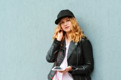 Young stylish woman in cap and leather jacket. Hipster girl listening favourite audio songs in earphones. Girl posing over grey. Wall, copy space. People royalty free stock images