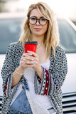 Young stylish woman in a city street near a white car.  Royalty Free Stock Photography