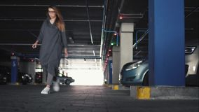 Young stylish woman closes the car and goes on a parking stock video
