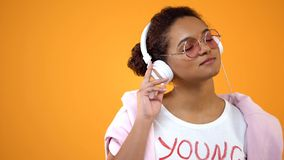 Young stylish woman enjoying favourite music in headphones, radio application. Stock photo royalty free stock image