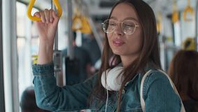 Young stylish woman enjoying trip in the modern tram, standing with coffee in the public transport.  stock video footage