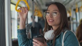 Young stylish woman enjoying trip in the modern tram, standing with coffee in the public transport. Young stylish woman enjoying trip in the modern tram stock footage