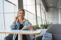 Young woman in glasses works at a table in a cafe. royalty free stock photos