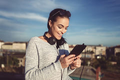 Young stylish woman with headphones and tablet outdoor Royalty Free Stock Photos
