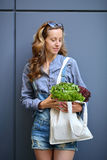Young stylish woman is holding in their hands a linen Bag with Lettuce Salad Stock Images
