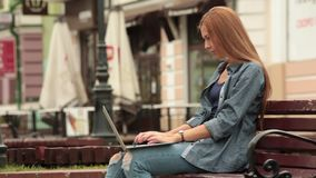 Young stylish woman with a laptop is sitting on a bench and working. The girl posing in the city streets. vacation europe stock video footage