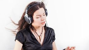 Young stylish woman in large headphones listening to music and having fun. Music lover girl with flying hair enjoys music royalty free stock photo