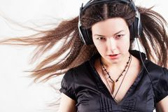 Young stylish woman in large headphones listening to music and having fun. Music lover girl with flying hair enjoys music royalty free stock image