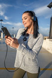 Young stylish woman listening music outdoor by tablet Royalty Free Stock Photography