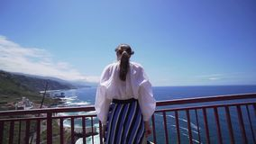 Young stylish woman looks at the Atlantic Ocean with a hat in her hands, stable shot. Beautiful girl on a sunny day on. The island of Tenerife fullhd stock video