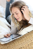 Young stylish woman lying on bed listening to music Stock Photography