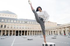 Young stylish woman in pants with split on street in Paris, France Stock Images