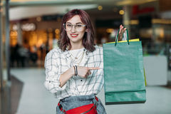 Young stylish woman pointing at shopping bags, boutique shopping concept. Happy young stylish woman pointing at shopping bags, boutique shopping concept Stock Photos
