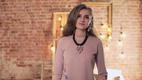 Young stylish woman posing against old brick wall. Girl defile in the loft interior. Young stylish woman posing against old brick wall. Girl is defiling on a stock video footage
