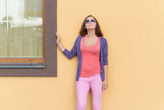 Young stylish woman posing against the wall. Stock Images