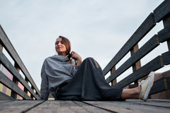 Young stylish woman resting on the bridge. Attractive girl with long hair sitting on wooden floor outside Royalty Free Stock Images