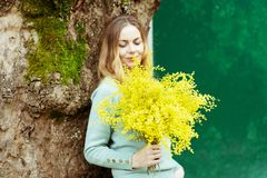 A young stylish woman is smiling, holding a present in her hand a bouquet of fresh mimosa flowers royalty free stock image