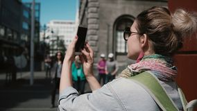 Young stylish woman standing on street and taking photo of the buildings. Female uses the smartphone for photographing.