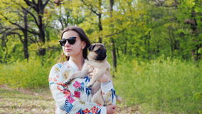 Young stylish woman in sunglasses walking in the park with a dog of pug breed. Holds a pet in his arms stock footage