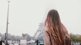 Young stylish woman taking photo of Eiffel tower in fog on smartphone. Girl traveling in Paris, France alone. stock video footage