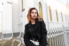 Young stylish woman in a trendy black coat in a T-shirt in trendy jeans with a leather handbag posing near a metal fence. On the background of a vintage royalty free stock image