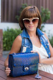 Young stylish woman in trendy outfit with snakeskin python luxury bag in hands. Woman with handbag near the swimming stock images
